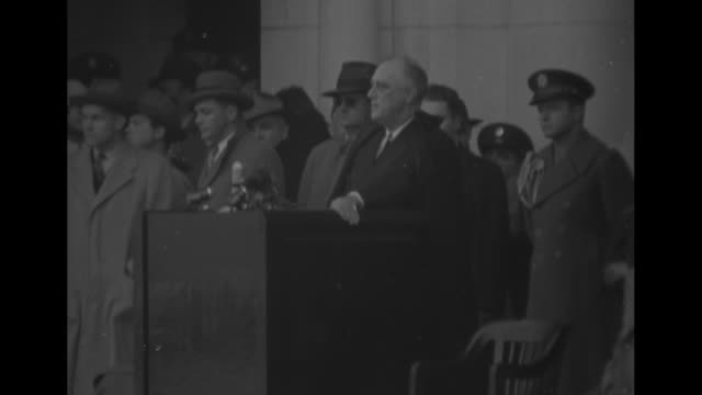 President Franklin D Roosevelt speaking at podium on Armistice Day group of officials behind him at Arlington National Cemetery