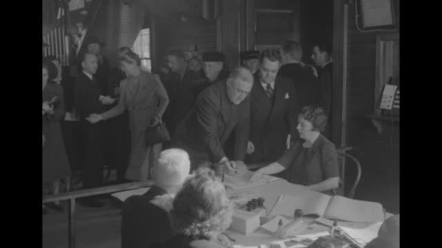 president franklin d. roosevelt stands at registration desk in hyde park's town hall, clerk asks his name and has him sign the book, he hands cane to... - röstsedel bildbanksvideor och videomaterial från bakom kulisserna