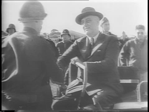 vídeos y material grabado en eventos de stock de president franklin d roosevelt wearing a fedora sits in a jeep surrounded by troops in sicily general dwight eisenhower to the left / presents... - general rango militar