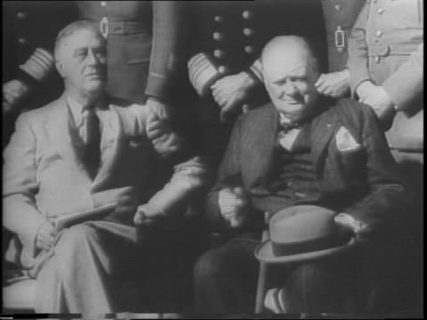 President Franklin Delano Roosevelt and Prime Minister Winston Churchill sit beside each other in front of military officers / close up of Roosevelt...