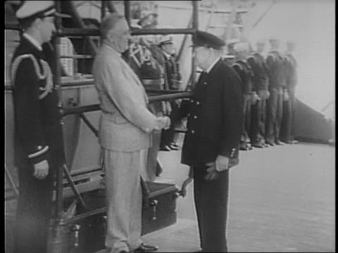 president franklin roosevelt and uniformed franklin roosevelt jr wait on the deck of a ship / several uniformed dignitaries file in and shake hands... - 1941年点の映像素材/bロール