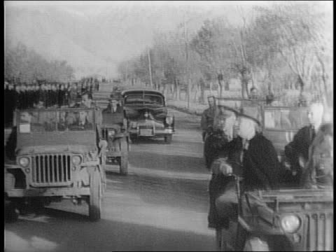 vídeos de stock e filmes b-roll de president franklin roosevelt pays a visit to us troops in camp amirabad, iran / roosevelt with entourage rides in jeep past troops, salutes / closer... - enfeites para a cabeça