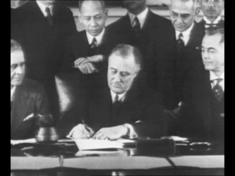 US President Franklin Roosevelt signs document approving a constitution for the Commonwealth of the Philippines in 1935 seated next to the President...