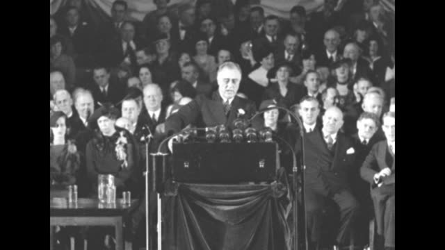 President Franklin Roosevelt speaking at podium with microphones in front part of audience sitting behind him Eleanor Roosevelt seated in front row...