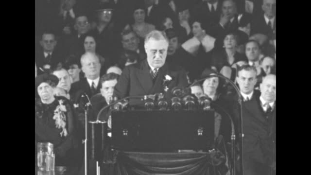 president franklin roosevelt speaking from behind podium with microphones he speaks of monopolies causing depression and federal government remedying... - new deal video stock e b–roll