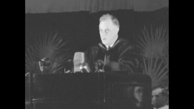 vidéos et rushes de president franklin roosevelt wearing academic regalia standing at podium begins speech university academics seated behind him can see backs of heads... - occupation