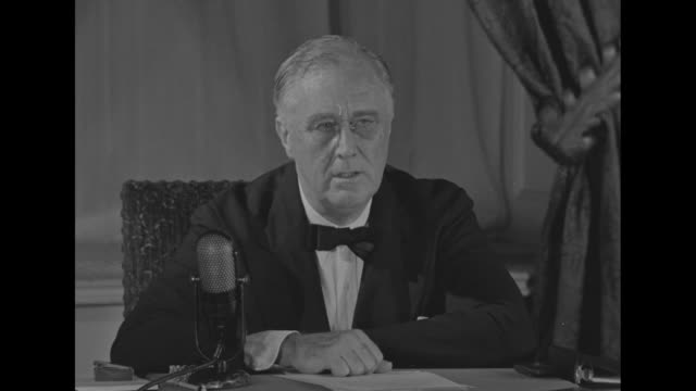 us president franklin roosevelt wearing black tie and pince nez and seated at desk before a microphone sot it is a great victory for the united... - 停戦点の映像素材/bロール