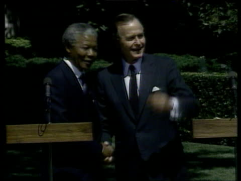 President George Bush Senior and Nelson Mandela at microphones they shake hands then walk off Washington DC 25 Jun 90