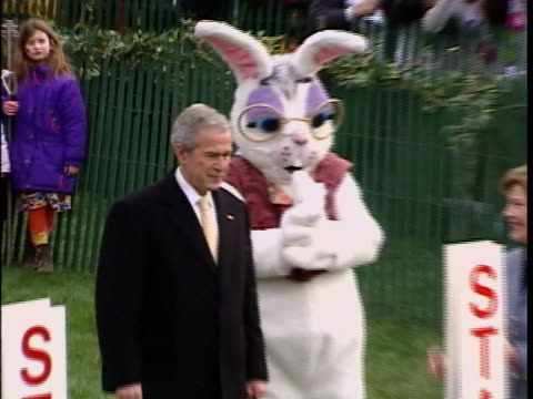 president george w. bush and first lady laura bush on the white house lawn with the easter bunny at the annual easter egg roll. - laura bush stock videos & royalty-free footage
