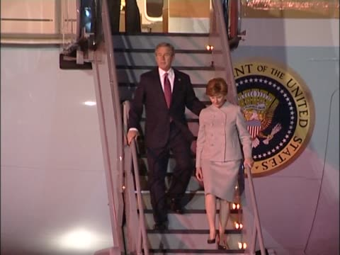 US president George W Bush and his wife Laura walk down steps of Air Force One to be greeted by Prince Charles at Heathrow at start of state visit to...