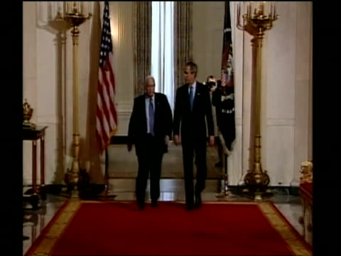 President George W Bush and Israel's Prime Minister Ariel Sharon walking along red carpet to face press White House Apr 04