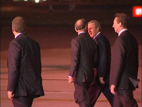 US president George W Bush talks to the Prince of Wales as he walks across Heathrow tarmac to helicopter at start of state visit to UK