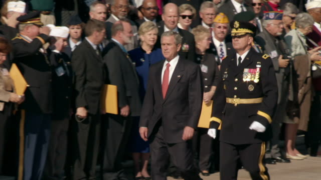 ws ts pan president george w bush walking next to uniform officer as veterans and others stand and watch during laying of wreath event at tomb of unknowns at arlington national cemetery on veterans day / washington, district of columbia, united states - präsident der usa stock-videos und b-roll-filmmaterial