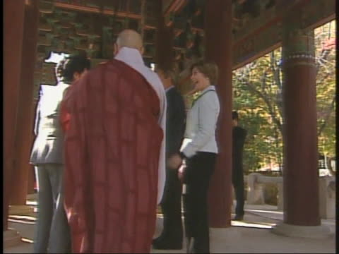 president george w. bush walks along with laura bush, south korean president roh moo-hyun and others under a pagoda. - roh moo hyun stock videos & royalty-free footage