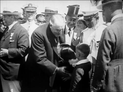 vídeos de stock, filmes e b-roll de president harding shaking hands awarding medals to immigrant children / newsreel - 1923