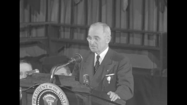 vídeos de stock, filmes e b-roll de president harry s truman at lectern at head table vips at table standing applauding then sitting world flags on stage behind them multitiered cake on... - presidente dos estados unidos