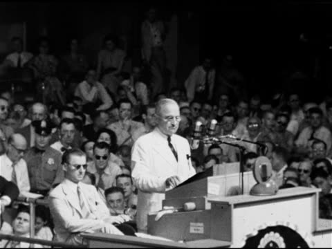 President Harry S Truman behind podium saying 80th Congress trying to dodge responsibilities not going to let them country can't afford another...