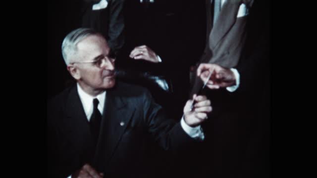 president harry s truman signing the north atlantic treaty behind him are sir derrick hoyes miller henrik de kauffman w d matthews louis johnson... - mature men stock videos & royalty-free footage