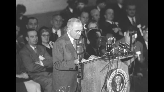 president harry s. truman speaks from podium that has kmo microphone on it, vip audience behind him at tacoma washington armory - 武器庫点の映像素材/bロール