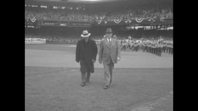 president harry s. truman walking down steps in stands at griffith stadium with surrounding spectators standing; he stops and shakes hands with boy... - surrounding wall点の映像素材/bロール