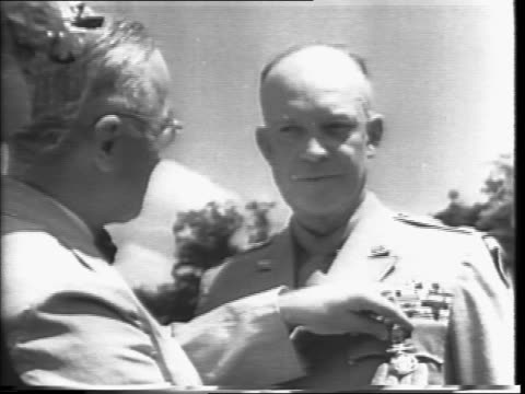 President Harry S Truman with Eisenhower and group walking out onto White House lawn / people watch / Dwight D Eisenhower receiving Distinguished...