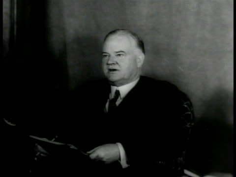 President Herbert Clark Hoover sitting in chair holding papers speaking to someone offcamera [possibly a cheat on time this might be his home office...