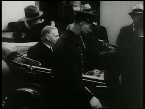 President Herbert Hoover seated in back of convertible w/ presidentelect Franklin D Roosevelt riding in open car to ceremony together procession to...