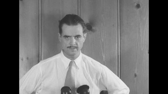 twa president howard hughes in shirt sleeves and checkered necktie prepares to speak / sot hughes speaks before three microphones directing a... - millionär stock-videos und b-roll-filmmaterial