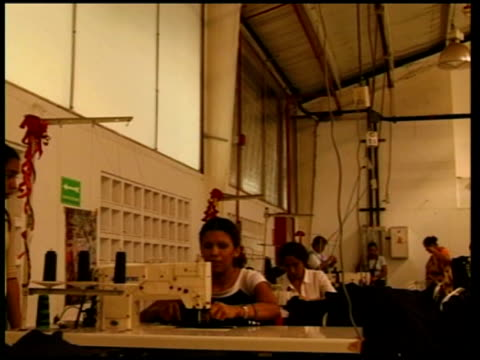 President Hugo Chavez and tensions with the US Caracas General views city slums Women working at sewing machines in shoe factory Factory workers...