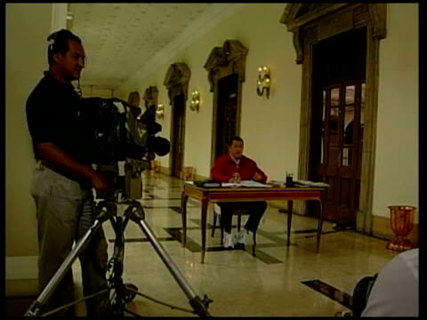 president hugo chavez and tensions with the us venezuela caracas chavez seated at table for weekly national address chavez at table tilt down wearing... - ウゴ・チャベス点の映像素材/bロール