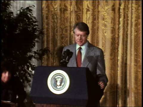 President JIMMY CARTER entering press conference with Zbigniew Brzezinski Coretta Scott King in the audience He takes podium gives speech to...