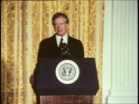 president jimmy carter enters a room in the white house for a press conference / he shakes hands with those standing on stage former first lady lady... - jimmy carter präsident stock-videos und b-roll-filmmaterial