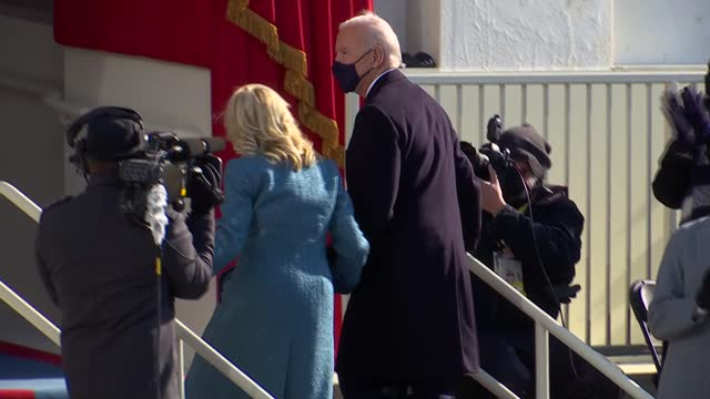 president joe biden accompanies first lady jill biden up steps from platform at west front of the us capitol after taking oath of office, delivering... - 就任式点の映像素材/bロール