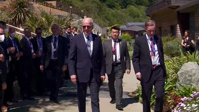 president joe biden, surrounded by his entourage, walks to the plenary session on final day of g7 summit in carbis bay, cornwall - walking stock videos & royalty-free footage