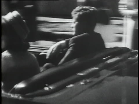 vídeos de stock e filmes b-roll de u.s. president john f. kennedy is assassinated as he rides in a motorcade with his wife in dallas, texas. - morte