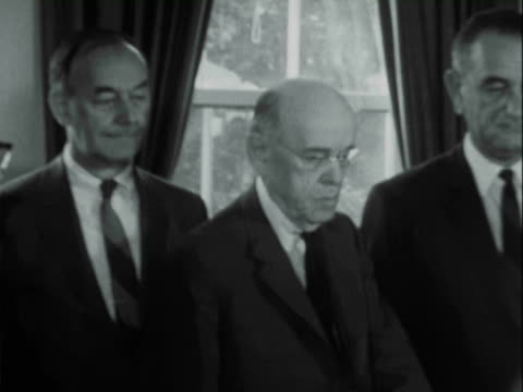President John F Kennedy sitting at desk in Oval Office of White House / surrounded by legislators including Vice President Lyndon Johnson /...