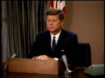 vidéos et rushes de president john f. kennedy sitting behind podium / washington d.c., united states - 1963