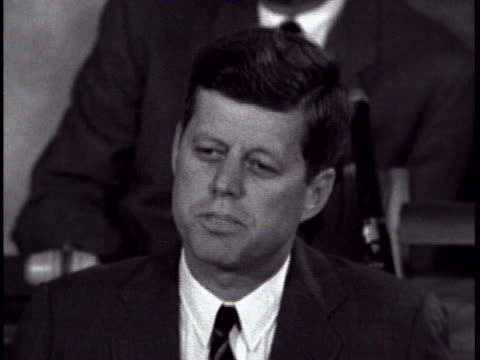 of president john f. kennedy, who is looking down at prepared remarks. he is wearing a dark suit and tie, and the torso of a man sitting behind him... - sputnik stock videos & royalty-free footage