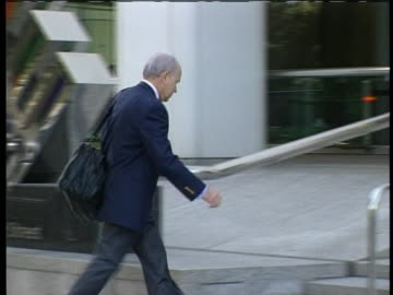 president ken lay walking to enron headquarters. there is a medium shot of ken lay walking towards the right of the screen up the stairs of enron... - lying down stock videos & royalty-free footage