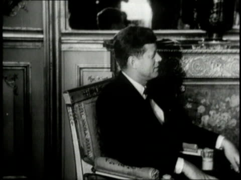 President Kennedy sitting in large room while French President Charles De Gaulle closes door and sits down / France
