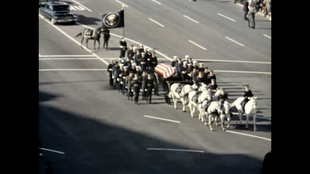 president kennedy's casket procession walks towards the capitol building / row after row of uniformed men march soberly down the streets of... - 棺点の映像素材/bロール