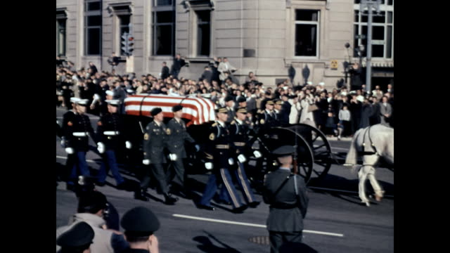 president kennedy's funeral procession comes down pennsylvania avenue / huge crowd of press people at top of street watching the procession get... - attentat auf john f. kennedy stock-videos und b-roll-filmmaterial
