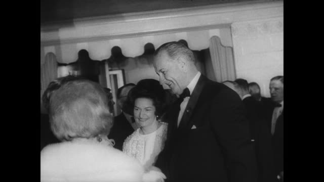 president lyndon b johnson and wife lady bird johnson arrive in new york for two dinner dances / shake hands with other guests in formal evening wear... - dinner lady stock videos & royalty-free footage