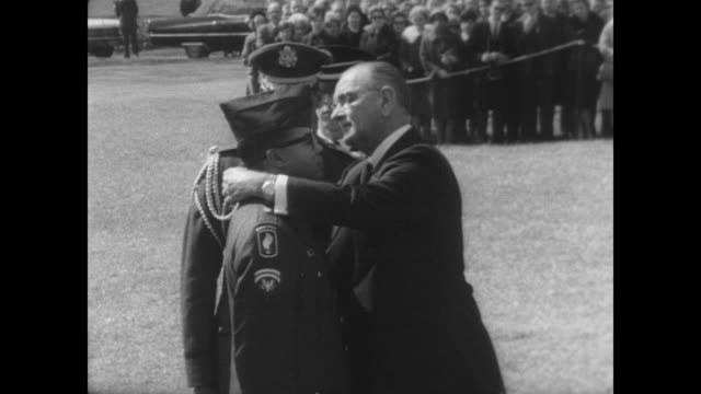 president lyndon b johnson clips the medal of honor around the neck of army medic lawrence joel of fayetteville at a ceremony at the white house /... - wife carrying stock videos and b-roll footage