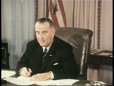 vidéos et rushes de president lyndon b. johnson signs documents in the oval office of the white house. - président