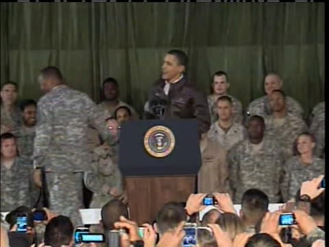 president obama shakes hands with soldiers and takes the podium before making a speech at bagram airfield, afghanistan in 2010. - bagram stock-videos und b-roll-filmmaterial