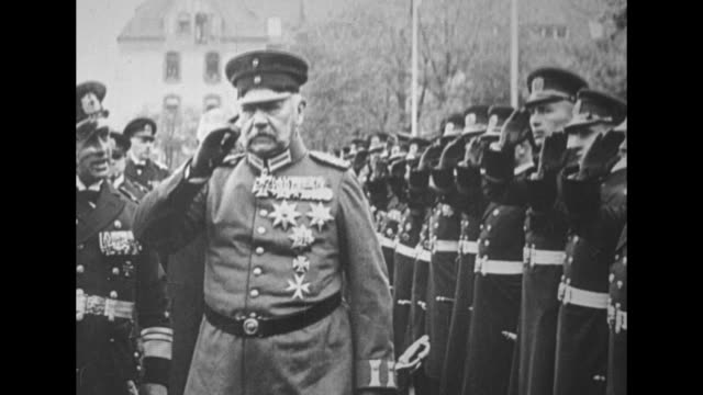 President of the German Reich Paul von Hindenburg in full military uniform conducts troop review approaches camera salutes / train car moves away...