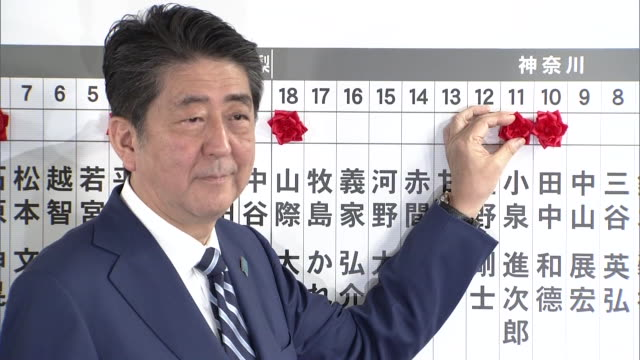 President of the Liberal Democratic Party Shinzo Abe putting flowers on a chart of indicating candidates winning a seat after the general election of...