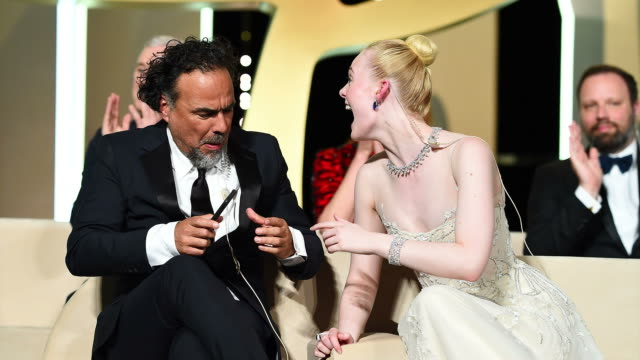 President of the Main competition jury Alejandro Gonzalez Inarritu and Jury Member Elle Fanning take a photo on stage at the Closing Ceremony during...