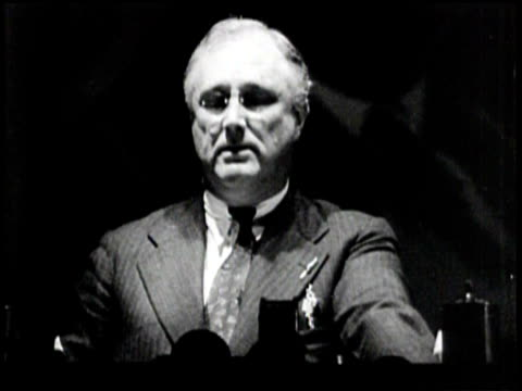 President Roosevelt on s stage with many others sips a glass of water / closer shot as he gives speech against Communism /